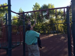 Mary Ashley crosses the monkey bars with a little help from Daddy